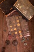 Vintage books and coins on old wooden table — Foto de Stock