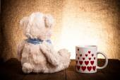 Teddy bear is sitting on the old wooden table. Mug with hearts — Stock Photo