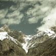 Clouds over the snow-covered tops of the rocks. Landscape. Toned — Stock Photo #63315531