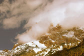 Clouds lie on the snow-covered tops of the rocks. Landscape. Ton — Stock Photo