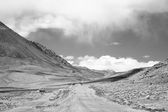 Road to clouds in valley in the foothills of the Fann mountains. — Fotografia Stock