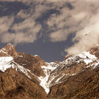 Clouds over the snow-covered tops of the rocks. Landscape. Toned — Stock Photo #63408067