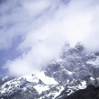 Clouds lie on the snow-covered tops of the rocks. Landscape. Ton — Stock Photo #63408089