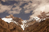 Clouds over the snow-covered tops of the rocks. Landscape. Toned — Fotografia Stock
