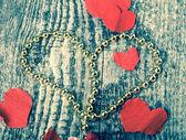 Πολλές καρδιές του Αγίου Βαλεντίνου και λαμπρές χάντρες στο παλιό ξύλινο τραπέζι. T — Φωτογραφία Αρχείου