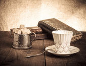 Cup of coffee, sugar bowl and stack of old books on the old wood — Zdjęcie stockowe