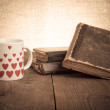 Old books and a cup with hearts on a wooden table — Stock Photo #63703025