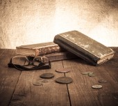 Vintage books and coins and spectacles on old wooden table. Tone — Стоковое фото
