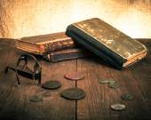 Vintage books and coins and spectacles on old wooden table. Tone — Zdjęcie stockowe