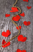 Many Valentine hearts and shiny beads on the old wooden table. — Stock Photo