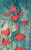 Many Valentine hearts and shiny beads on the old wooden table. T — Stock Photo