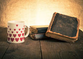 Old books and a cup with hearts on a wooden table — Stock Photo