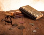 Vintage books and coins and spectacles on old wooden table. Tone — Stockfoto