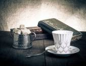 Cup of coffee, sugar bowl and stack of old books on the old wood — Stock Photo