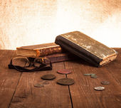 Vintage books and coins and spectacles on old wooden table. Tone — Stock Photo