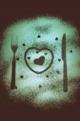 Silhouettes of fork, knife and hearts on the flour on a black ba — Stock Photo