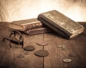 Εκλεκτής ποιότητας βιβλία και κέρματα και θεάματα στο παλιό ξύλινο τραπέζι. Τόνος — Φωτογραφία Αρχείου