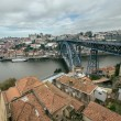 Red tiled roofs, metal bridge, old houses and the river Douro in — Stock Photo #64314719