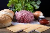 Meat, cheese, onions, herbs, salt, ketchup on a wooden table ove — Stock Photo
