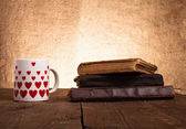 White mug with many pictured hearts and stack of old books on th — Foto Stock