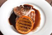 Carne alla griglia con salsa all'arancia su un piatto bianco — Foto Stock