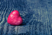 Shiny red heart on old wooden background. Toned — Stock Photo