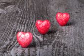 Three shiny red hearts on old wooden background — ストック写真