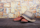 Straw hat and moccasins on a wooden table in front of a stone wa — Stock Photo