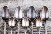 Antic metal spoons on old wooden board. Selective focus — Stock Photo