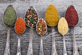 Antic metal spoons with different kinds of spices on old wooden  — Stock Photo