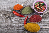 Antic metal spoons and small bowl with different kinds of spices — Stock Photo