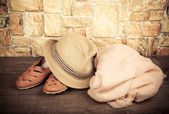 Straw hat, pink scarf and moccasins on a wooden table in front o — Stock Photo