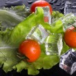 Red cherry tomatos, green salad and ice cubes on black wet table — Stock Photo #73574927