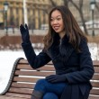 Smiling Asian girl on a Park bench waving — Stock Photo #66026213