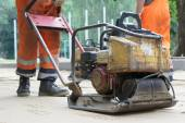 Plate compactor prepares sandy surface. — Stock Photo