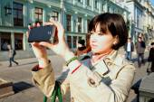 Girl photographs a smartphone on the street. — Stock Photo