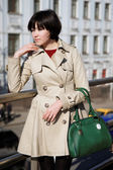 Jovem mulher com uma bolsa verde, foto vertical. — Fotografia Stock