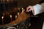 Woman hand lighting candles in a church — Stock Photo