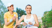 Joyful girlfriends in sports clothing drinking water, — Stock Photo