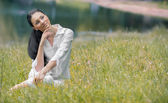 Young relaxing woman sitting in the grass — Stock Photo