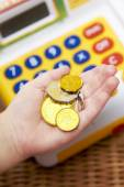 Child's Hand Holding Pretend Coins Next To Toy Cash Register — Stock Photo