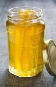 Jar Of Honey With Honeycomb On Wooden Surface — Стоковое фото