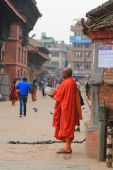 A Buddhist monk waiting for donated money in the Durbar Square, Nepal — Stock Photo