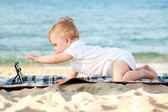 Baby med Tabletpc på stranden. — Stockfoto