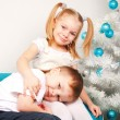Happy kids cuddling near Christmas tree. — Photo #55623895