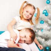 Happy kids cuddling near Christmas tree. — Stock Photo