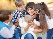 Large family hugging and having fun outdoors — Stock Photo