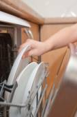 Child's hand put plate in dishwasher — ストック写真