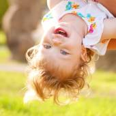 Happy baby playing upside down. — Stock Photo