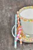 Glass of milk with striped straws — Stock Photo